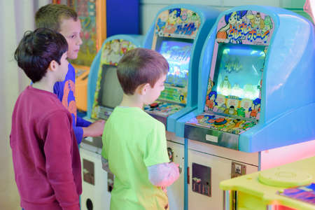 machines: KFAR SABA, ISRAEL - DEC. 12, 2015: 8 year old kids having fun at the arcade with video games, lottery machines, tickets, and prizes.