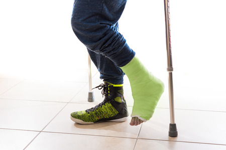 accident patient: Young man with a broken ankle following a basketball accident, walking on crutches with a modern high-top basketball shoe and a matching yellow - green cast (isolated on white)