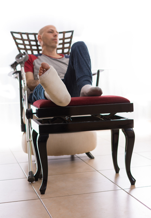 jewish home: Young man with a broken ankle and a white cast on his leg, sitting on a couch, with crutches nearby, looking sad and frustrated