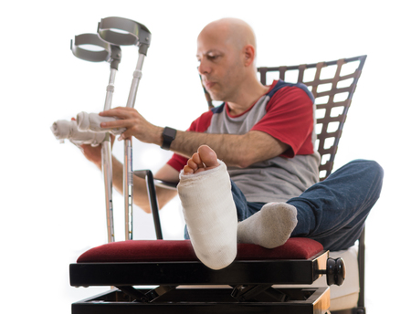 Young man with a broken ankle and a white cast on his leg, putting down his crutches after sitting on a couch and ottoman