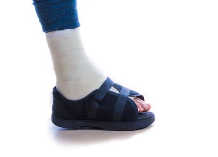 pierna rota: Hombre joven con un tobillo roto y un elenco blanco y zapato para yeso (sandalia) en la pierna, caminar con muletas (aislado en blanco)