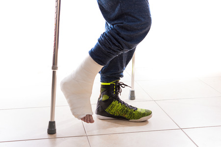broken foot: Young man with a broken ankle and a white cast on his leg following a basketball accident, walking on crutches with a modern high-top basketball shoe (isolated on white)