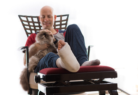 jewish home: Young man with a broken ankle and a white cast on his leg, sitting on a couch, with crutches nearby, petting and getting some comfort from his cat