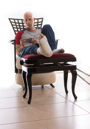 web cast: Young man with a broken ankle and a white cast on his leg, sitting on a couch, with crutches nearby, surfing the web on his phone