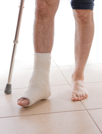 foot pain: Young man with a broken ankle and a white cast on his leg, walking on crutches (isolated on white) Stock Photo