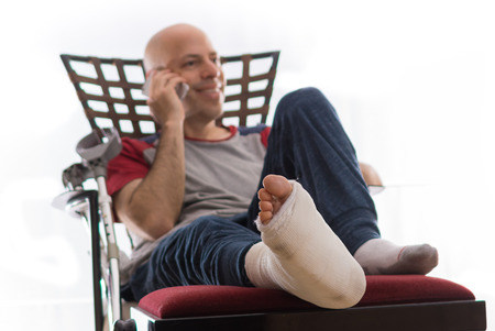 accident patient: Young man with a broken ankle and a white cast on his leg, sitting on a couch, with crutches nearby, happily talking on his phone