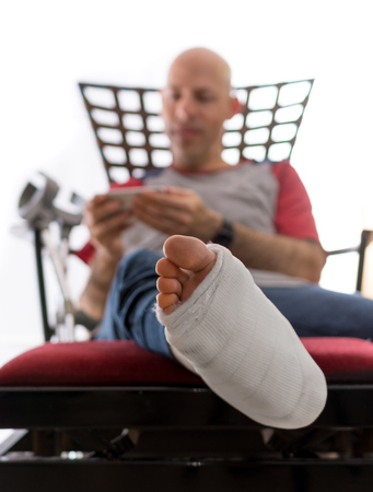 web cast: Young man with a broken ankle and a white cast on his leg, sitting on a couch with crutches nearby, surfing the web on his phone