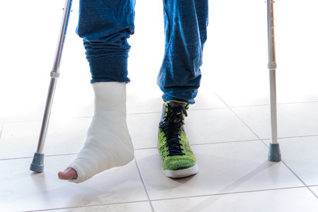 accident patient: Young man with a broken ankle and a white cast on his leg following a basketball accident, walking on crutches and a high-top basketball shoe (isolated on white) Stock Photo