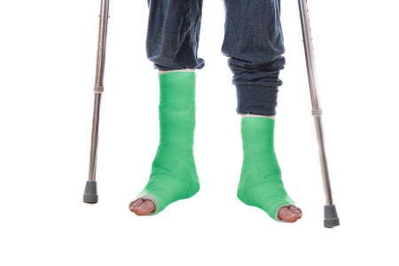 ankles: Young man with two broken ankles and dual green casts on his legs, leaning on crutches  (isolated on white)