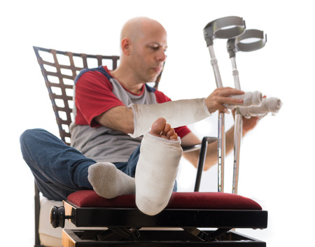 broken wrist: Young man after a bad accident with broken ankle and wrist and white plaster and fiberglass casts on his leg and arm, putting down his crutches after sitting on a couch