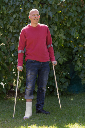 Young man with a broken ankle and a white fiberglass and plaster cast on his leg, getting some fresh air in the garden while walking on crutches  (back-light)