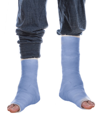 dual: Young man with two broken ankles and dual blue casts on his legs(isolated on white)