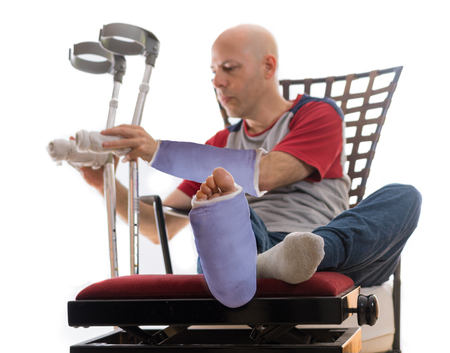 Young man after a bad accident with broken ankle and wrist and blue plaster and fiberglass casts on his leg and arm, putting down his crutches after sitting on a couch Standard-Bild