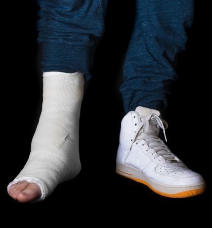 accident patient: Young man with a broken ankle and a white cast on his leg following a basketball accident, walking on crutches with a high-top basketball shoe (sneaker) (isolated on black)