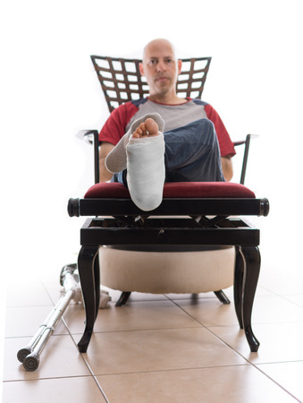 jewish home: Young man with a broken ankle and a white cast on his leg, sitting on a couch, with crutches nearby, looking bored
