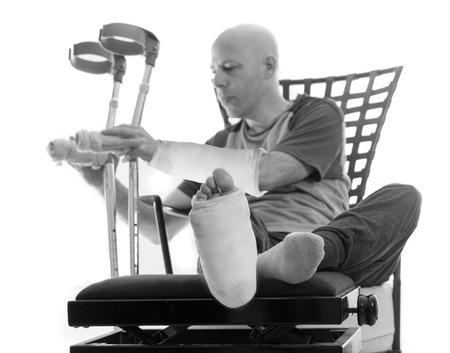fibra de vidrio: El hombre joven después de un accidente grave con fractura de tobillo y la muñeca y yeso y fibra de vidrio arroja sobre su pierna y el brazo, dejando las muletas después de estar sentado en un sofá (blanco y negro) Foto de archivo