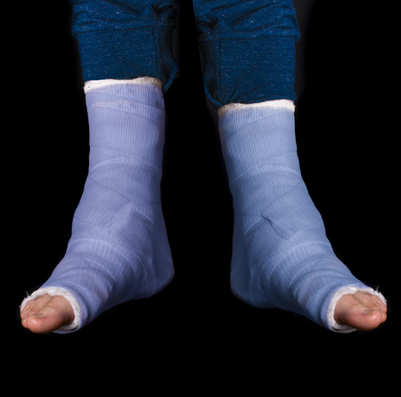 dual: Young man with two broken ankles and dual blue casts on his legs  (isolated on black)