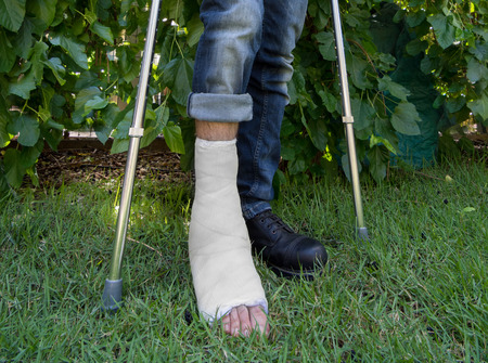 plaster leg cast: Young man with a broken ankle and a white fiberglass and plaster cast on his leg, getting some fresh air in the garden while walking on crutches (wide angle shot) Stock Photo
