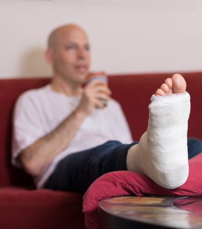 jewish home: Young man with a broken ankle and a white cast on his leg, sitting on a red couch drinking water (selective focus) Stock Photo