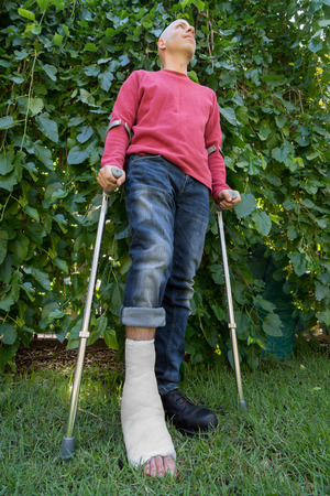 fiberglass: Young man with a broken ankle and a white fiberglass and plaster cast on his leg, getting some fresh air in the garden while walking on crutches (wide angle shot) Stock Photo