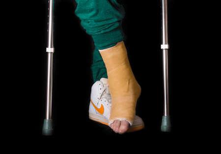 fiberglass: NUEVA YORK - 18 de mayo de 2016: El hombre joven con un tobillo roto y un elenco de color naranja en la pierna tras un accidente de baloncesto, caminar con muletas con una forma de bota Nike zapatillas de baloncesto (editorial ilustrativo) Foto de archivo