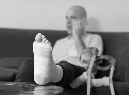 web cast: Young man with a broken ankle and a white cast on his leg, sitting on a red couch, surfing the web on his phone (selective focus)