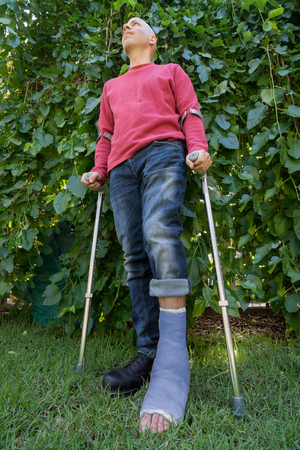 fiberglass: Young man with a broken ankle and a blue fiberglass and plaster cast on his leg, getting some fresh air in the garden while walking on crutches (wide angle shot)