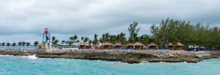 cay: Colorful cabins, tower, and palm trees on a tropical Caribbean beach in Coco Cay, Bahamas Stock Photo
