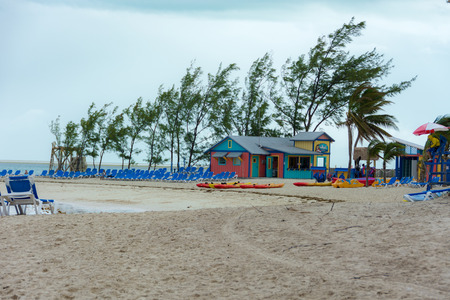 cay: COCO CAY, BAHAMAS - OCT 16, 2016: Colorful cabins, tower, palm trees and sand with water sports equipment on a tropical Bahamas beach