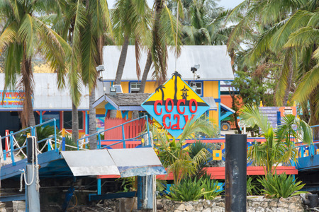 cay: COCO CAY, BAHAMAS - OCT 16, 2016: Sign welcoming visitors to the colorful Coco Cay island with palm trees and gangway waiting for the boat