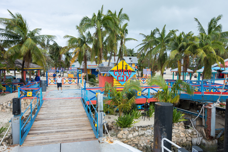 cay: COCO CAY, BAHAMAS - OCT 16, 2016: Sign welcoming visitors to the colorful Coco Cay island with palm trees and gangway waiting for the shuttle boat Editorial