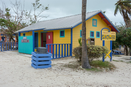 showers: COCO CAY, BAHAMAS - OCT 16, 2016: Colorful and fun restrooms water closet showers cabins on the Caribbean beach