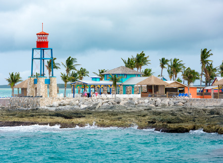 COCO CAY, BAHAMAS - OCT 16, 2016: Colorful cabins, tower, beach, and palm trees on a tropical Bahamas beach