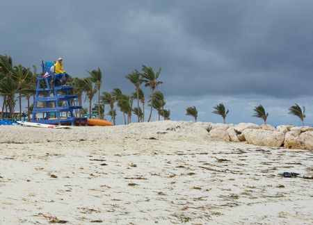 cay: COCO CAY, BAHAMAS - OCT 16, 2016: A lifeguard on a cloudy and windy day on the beach of the tropical paradise private island of Coco Cay in the Bahamas