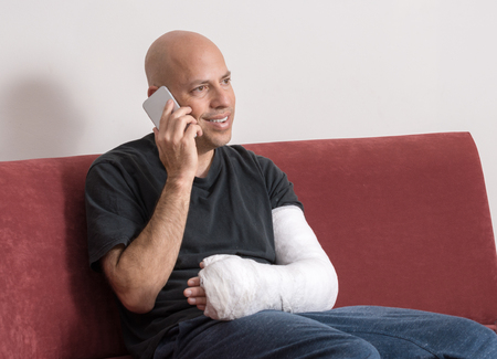 fibra de vidrio: Young man with an arm and elbow in a white plaster  fiberglass cast at home, happily talking on his phone after having broken his arm
