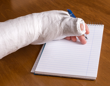 Person wearing an arm cast after breaking their wrist trying to write a note on a piece of paper Stock Photo