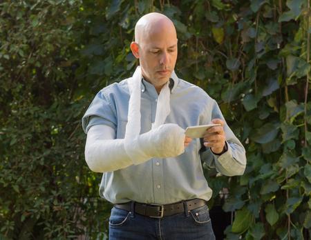fibra de vidrio: Hombre joven con un brazo y el codo en un yeso blanco  fibra de vidrio de pie en un jardín de mensajes de texto en su teléfono Foto de archivo