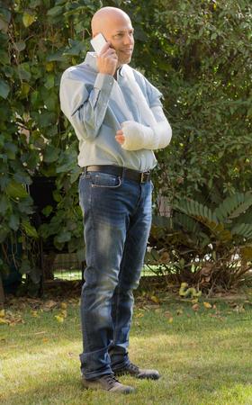 fibra de vidrio: Hombre joven con un brazo y el codo en un yeso blanco  fibra de vidrio de pie en un jardín, feliz hablando por su teléfono