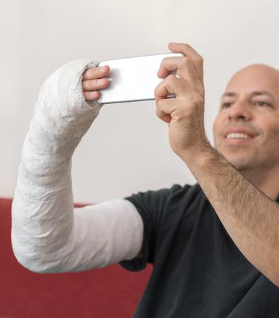 fibra de vidrio: Hombre joven con un brazo y el codo en un yeso blanco  fibra de vidrio emitidos en casa, hablando una autofoto en su teléfono inteligente mientras se recupera de una fractura en el brazo Foto de archivo