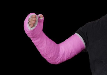 Close up of a pink  long arm plaster  fiberglass cast covering the wrist, arm, and elbow after a n accident, isolated on black