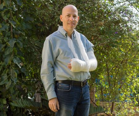 fibra de vidrio: Hombre joven con un brazo y el codo en un yeso blanco  fibra de vidrio de conseguir un poco de aire fresco en el patio trasero