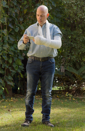 Young man with an arm and elbow in a white plaster  fiberglass standing in a garden texting on  his phone