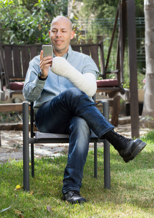 fibra de vidrio: Young man with an arm and elbow in a white plaster  fiberglass sitting in a garden texting on  his phone Foto de archivo