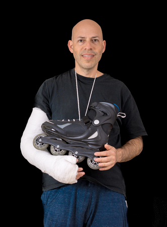 Young man sporting a bright white arm cast, holding an inline skate after a breaking his arm in a rollerblading accident, isolated on black Stock Photo