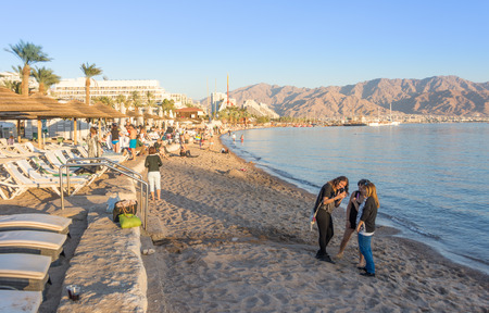 EILAT, ISRAEL - DEC. 29, 2016: People spending their Christmas and New Year vacation bathing on the Red Sea beach of sunny Eilat, Israel