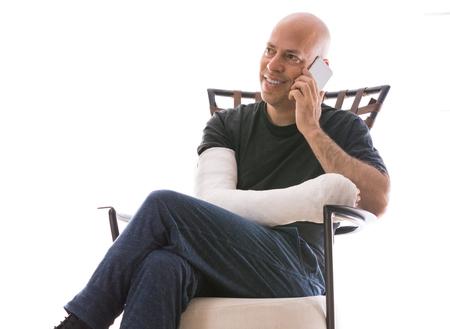 fibra de vidrio: Hombre joven con un brazo y el codo en un yeso blanco  fibra de vidrio emitidos sentado en un sofá moderno, feliz hablando por su teléfono después de haber roto el brazo Editorial