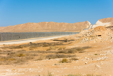 The new border fence between Israel (Negev Desert) and Egypt (Sinai Desert) with the patrol road protecting the border Stock Photo