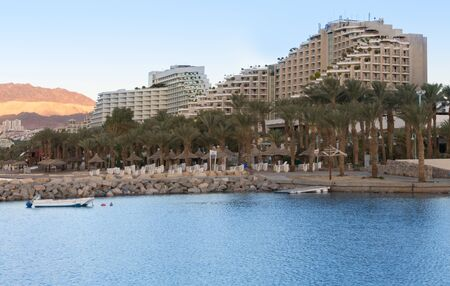 bordering: Hotel resort area of the Eilat harbor on the Red Seas Gulf of Aqaba at sunrise.  Eilat is Israels main vacation resort bordering between the Red Sea and Negev Desert. Stock Photo
