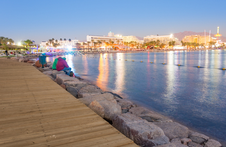 Sunset and blue hour at the Eilat boardwalk on the Red Seas Gulf of Aqaba with Eilats hotels in the background. Eilat is Israels main vacation resort bordering between the Red Sea and Negev Desert.