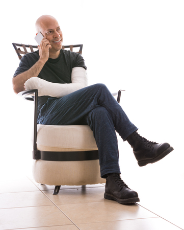 Young man with an arm and elbow in a white plaster  fiberglass cast sitting on a modern couch, happily talking on his phone after having broken his arm